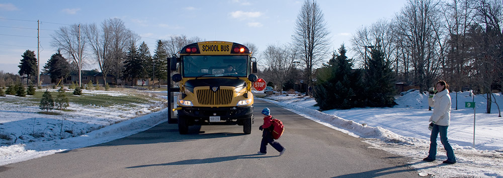 Boy crossing street in front of school bus