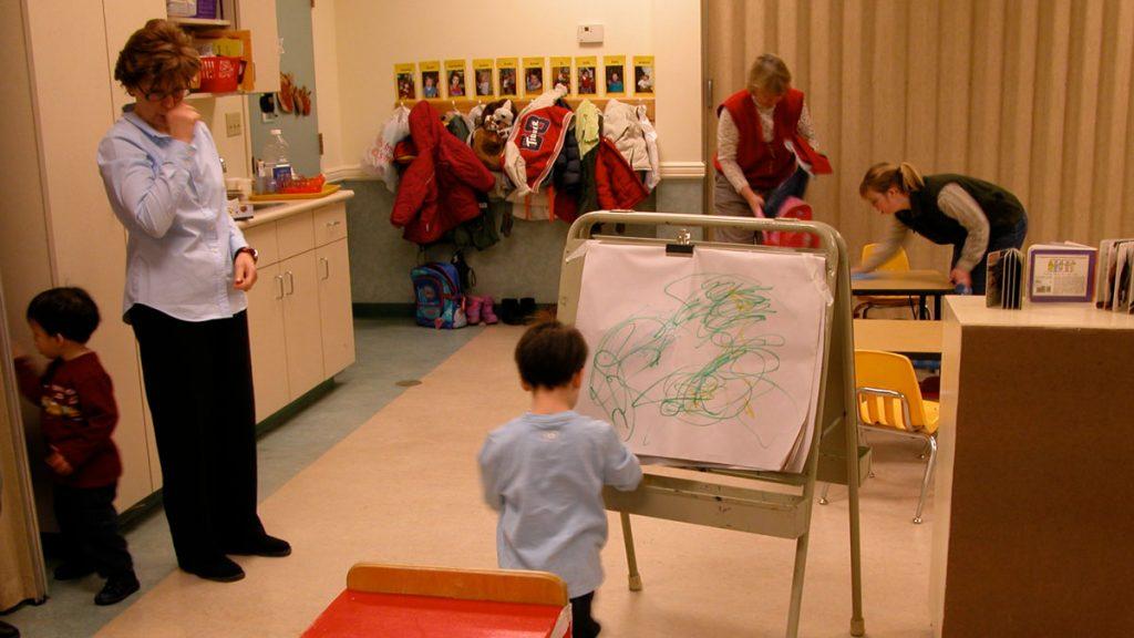 Teacher observes child drawing