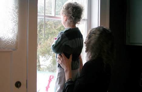 photo of mother and child looking out window