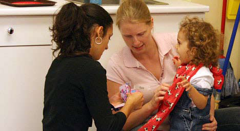 photo of daycare teachers showing a child a visual sequence